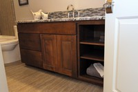 Thumb vanity  contemporary style  beech  dark stain  recessed panel  wide frame  full overlay  open cubbies  single sink  2