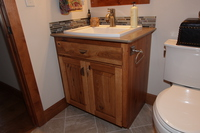 Thumb vanity  rustic style  knotty hickory  medium color  raised panel  single sink  standard overlay