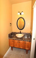 Thumb vanity  shaker style  knotty alder  medium color  recessed panel  tapered legs   feet  vessel sink  standard overlay