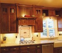 Thumb kitchen  craftsman style  quarter sawn oak  dark color  recessed panel doors  craftsman glass grid at the top  flush mount construction   13 bungalow crown  custom wood hood  apron front sink  upper above the window