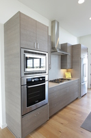 Thumb kitchen  contemporary style  custom laminate  grey   banded door  frameless construction  chimney hood  micro oven cabinet  bank of drawers