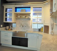 Thumb kitchen  contemporary style  painted with accent color walnut  hybrid construction  recessed panel and savannah doors  bank of drawers  glass doors  glass back with lights  apron sink