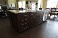 Thumb kitchen  contemporary style  quartersawn walnut  banded door  dark color  bank of drawers  horizontal grain  full overlay