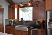 Thumb kitchen  craftsman style  cherry  medium color  recessed panel  craftsman glass grid door panel at the top  farm sink  apron sink  tall cabinet  full overlay