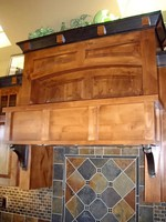 Thumb kitchen  craftsman style  knotty alder  raised and recessed panel  medium color with accent crown blocks on  7 crown  custom wood hood
