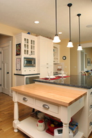 Thumb kitchen  craftsman style  painted  recessed panel  flush mount  butcher block top  table style island  turned legs  posts  deep microwave upper to the countertop  glass grid doors