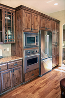 Thumb kitchen  traditional style  knotty alder  dark color  raised panel  double panel doors on the pantry  oven next to refrigerator  standard overlay