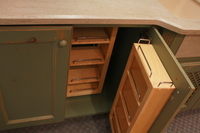 Thumb kitchen  traditional style  knotty alder  green paint with sand through and distress  recessed panel doors  chefs pantry shelves  baking center