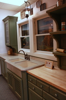 Thumb kitchen  traditional style  knotty alder  green painted with sand through and distress  lattice panel doors  open shelves with  8 ogee supports corbels  baking center   30 crown  standard overlay