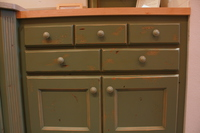 Thumb kitchen  traditional style  knotty alder  green painted with sand through and distress  recessed panel doors  2 rows of drawers over doors  baking center  butcher block top  3 top drawers  standard overlay