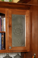Thumb kitchen  traditional style  knotty alder  recessed panel with punched tin door panel  medium color  edgewear on the doors  cove at bookcase opening   28 crown