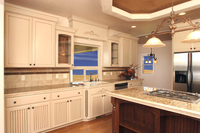 Thumb kitchen  traditional style  painted and glazed  recessed panel and wainscot panels  accent color island in walnut  arched glass panel doors  wainscot backs  turned posts or legs  onlays  standard overl