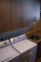 Thumb laundry or utility  contemporary style  frameless construction  custom laminate  grey color  banded doors  upper above the washer and dryer and shorter upper above the sink