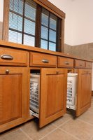 Thumb laundry or utility  craftsman style  quartersawn oak  raised panel doors with bevel drawer fronts  medium color  pull out hampers  standard overlay